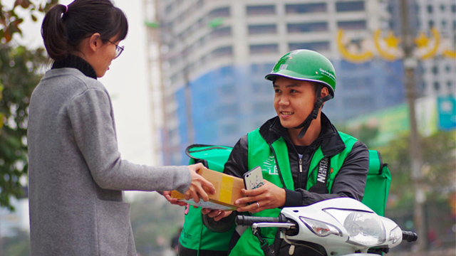A delivery man hands a customer an online order